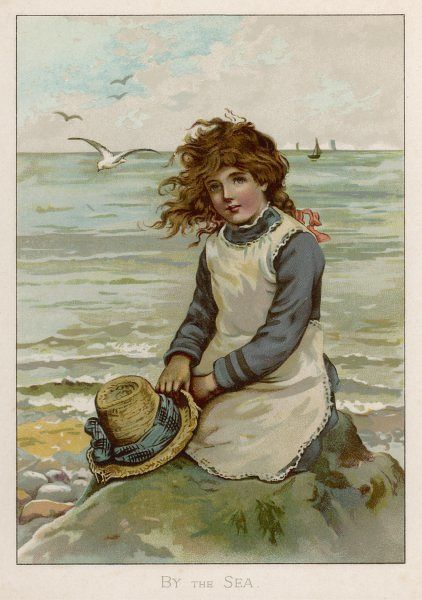 A little girl sits on a rock by a windy sea, holding her straw hat