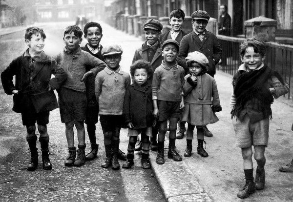 A group of working class children, black and white, playing together on 'Crown Street', probably in Acton, London W3