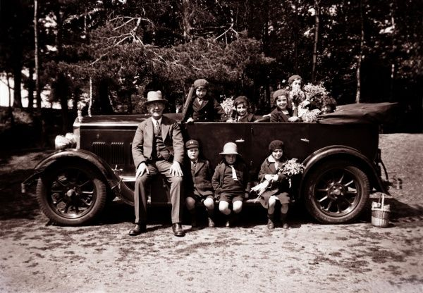 A mass of children and an older man surround and sit inside a Morris Empire Oxford 4-seater Tourer, some of the children are holding bunches of Flowers