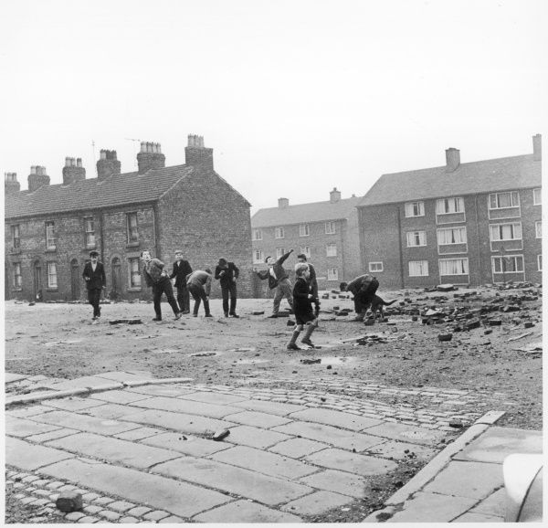 Children in a deserted Liverpool street throw bricks and rubble