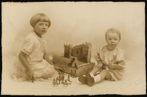 Two children play with their toy soldiers and their castle