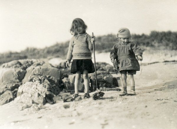 Two little children with their toys on a beach, somewhere in Scotland