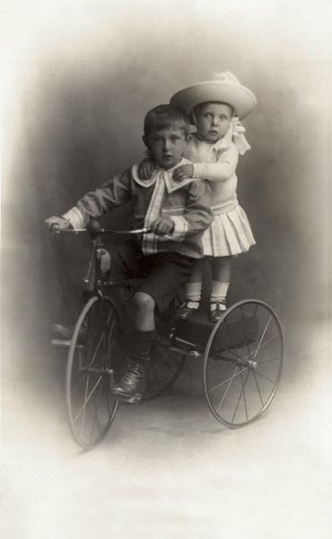 Two adorable children pose for their picture while riding a smart looking tricycle. A little boy in his finest Sunday best outfit takes charge of steering and the pedals while his adorable younger sibling stands on the back seat
