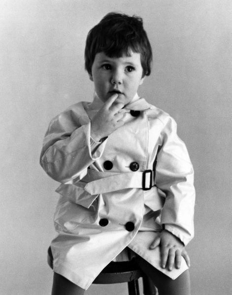 A little boy in a raincoat. Date: late 1960s