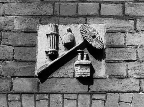 A quaint stone carving over a doorway at Benstead Hall, Stanstead Mountfitchet, Essex, England. It depicts a chimney sweep's brush and canes, bag of soot and a chimney pot. Date