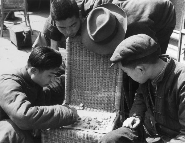 Teenage boys in Shanghai, China, playing Chinese Checkers or a similar board game. Date: 1930s