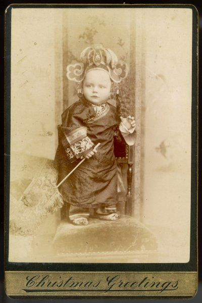 A little boy poses on a chair resplendent in a Chinese costume complete with head-dress, looking for all the world like a little emperor