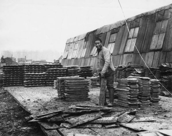 A Chinese worker salvaging tank track plates at the British Tank Corps Central Workshops, Teneur, northern France, during the First World War. Date: 1917