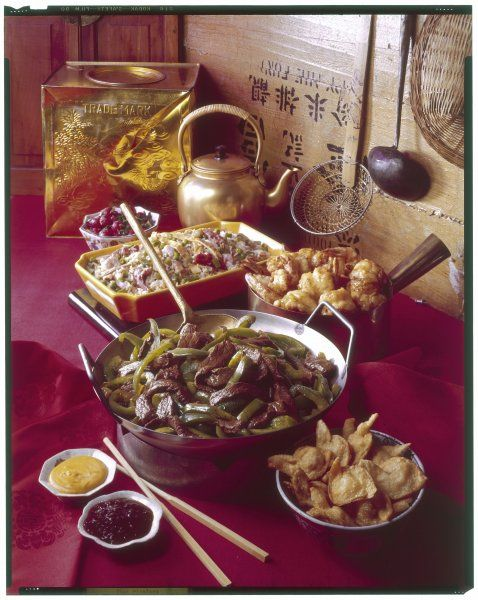 A Chinese meal, the main dish (in the wok) being beef with onions and green peppers. Note also the sweet and sour sauces and the obligatory chopsticks