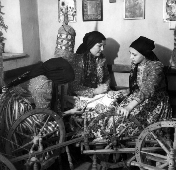 Women of Chodenland, (Bohemia, Czechoslovakia), spinning flax at their humming spinning wheels, singing folk songs as they spin in their colourful red dresses. Date: 1930s