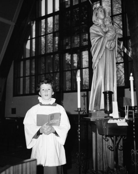 A choirboy singing solo in front of a modern stained glass window at Salfords Church, Horley, Surrey. He is holding a book entitled 'English Praise'. There is a statue of the Virgin Mary and Child next to him