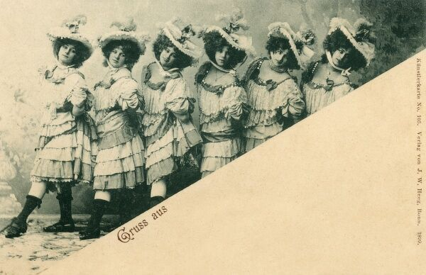 Chorus Line of German Dancing Girls, wearing many-layed dresses and large wide bonnets