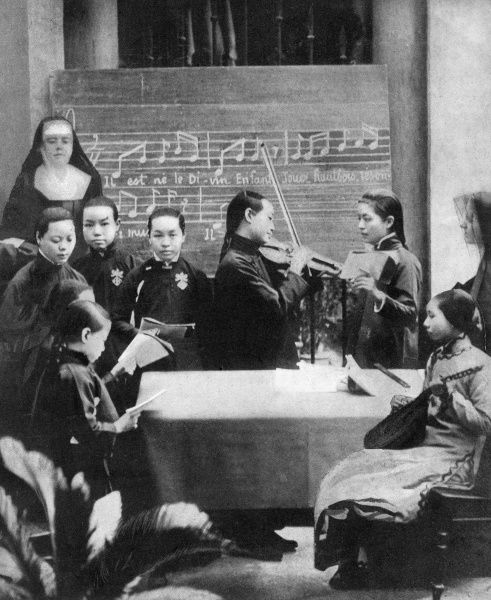 Young Chinese girls at a Roman Catholic school of music in Canton, being taught to play Christmas carols by French nuns. Date: 1911