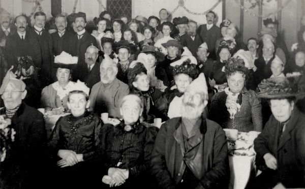 A Christmas celebration at Hastings workhouse, Sussex, with inmates and staff wearing a variety of hats