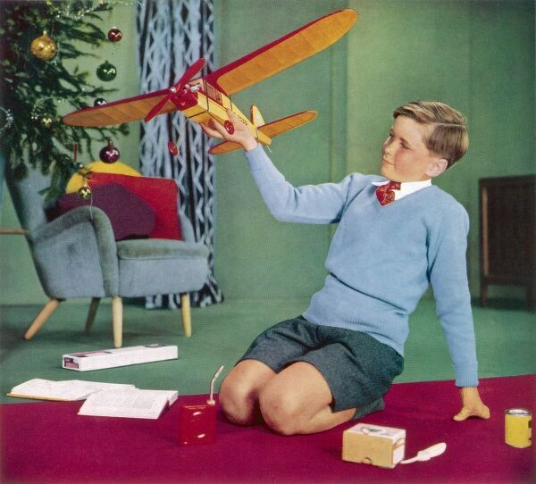 Colour photograph taken from an advertisement for Midland Bank gift cheques, showing a young boy playing with a toy plane on Christmas morning