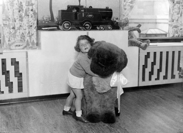 A lucky little girl cuddles a huge cuddly toy dog in a nursery full of other Christmas toy trains, teddies, etc. Date: early 1930s