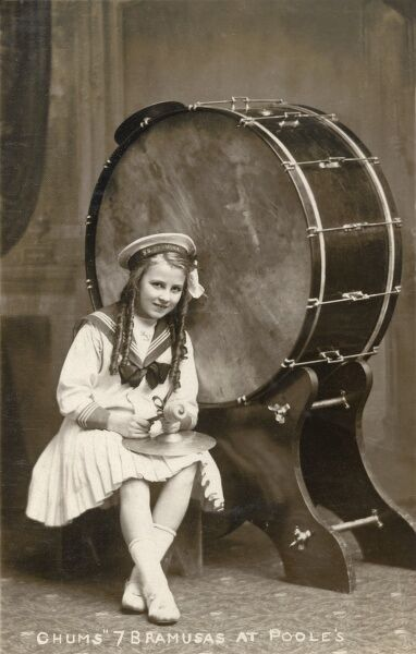 Young girl in a sailor suit wearing the cap of the SS Bramusas holding a beater and cymbal and sat beside a large bass drum