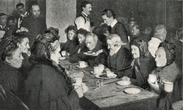 A number of elderly men and women awaiting admission to one of London's workhouses are provided with a meal by the Church Army