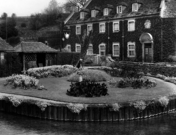 The Water Garden, a circular, lawned island garden, and the 'Swan' Hotel, Bibury, in the Cotswolds, Gloucestershire, England. Date: 1950s