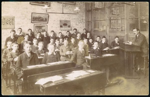 The First Class of boys at a boys' junior school, with their teacher sitting at a desk on the right