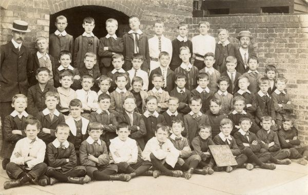 Class 3 of the New Road Boys pose for a photograph with their teacher who is wearing a boater
