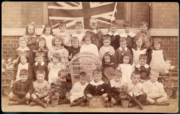 A primary school class have their photograph taken in front of a union jack flag. They have even brought the bird in its cage out to be in the picture