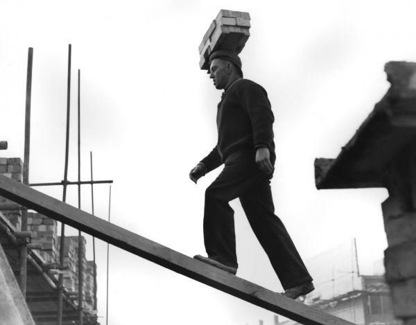 This bricklayer has come up with a nifty way to carry his bricks. Date: late 1960s