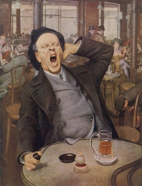 A man enjoying a glass of beer and a pipe yawns contentedly as he sits at a table on his own in a bar or pub