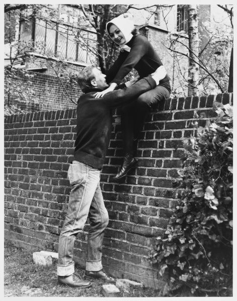 A man helps a woman up onto a wall