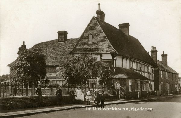 A timber framed building in Headcorn, known as the Cloth Hall, believed to have once served as the parish workhouse. Children stand on the pavement in front of some railings