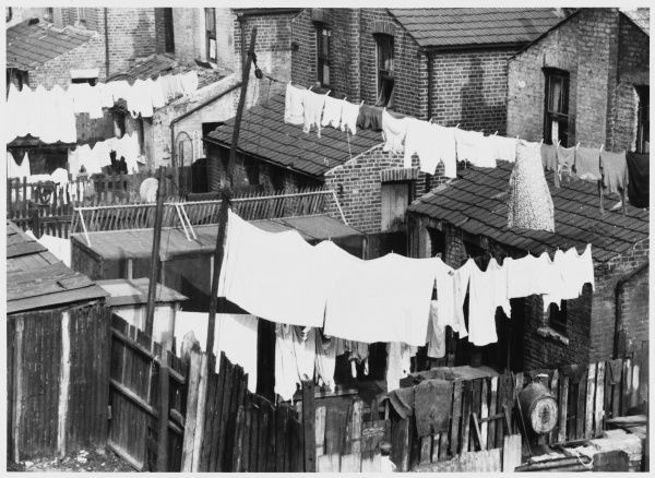 Drying sheets and general washing in the back yards of a row of terraced houses in London