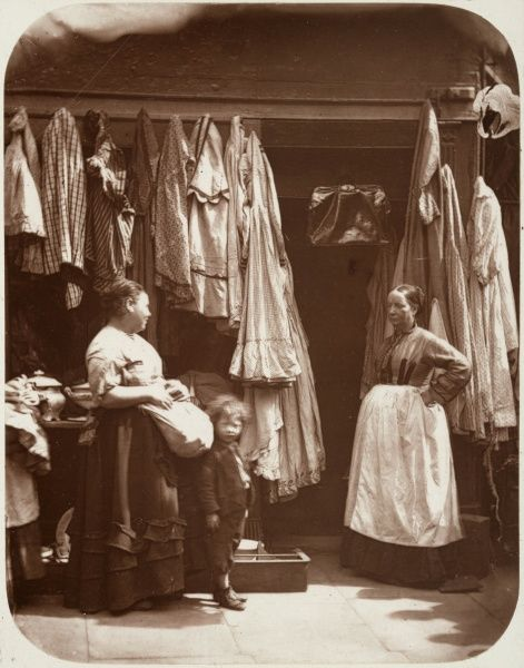 Two women, one with a small boy pass the time of day outside a women's clothes shop