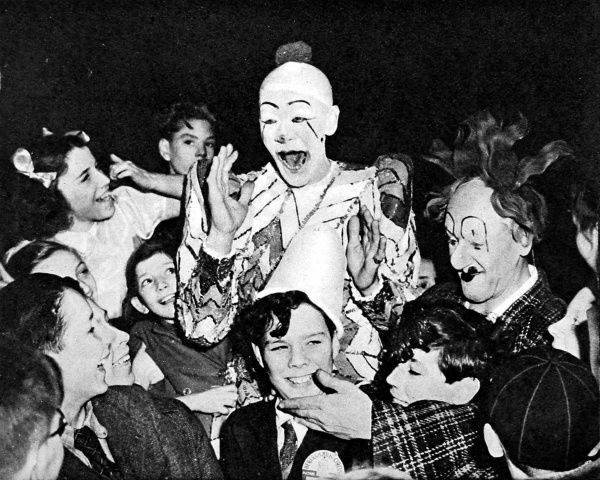 Photograph showing two clowns and a group of children at the circus in 1948
