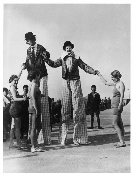 Two clowns on stilts, assisted by girls in bathing costumes, at Ramsgate, Kent, England