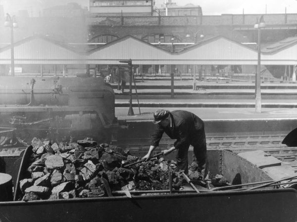 A railway worker putting coal into a tender, a scene at Liverpool Street Station, London, England