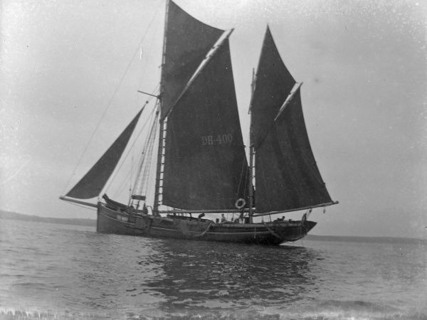 A coastal trader, number DH400, sailing along the River Usk off Newport, Gwent, Monmouthshire, South Wales