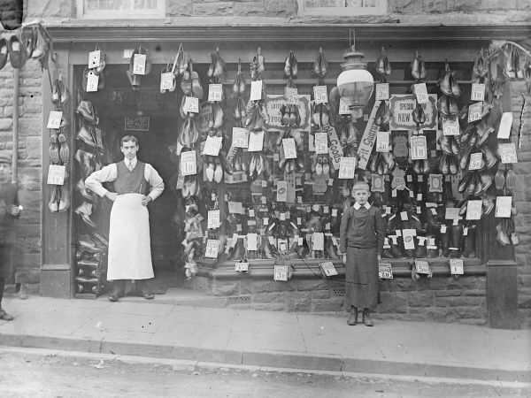 View of a cobbler's shop front in St David's, Pembrokeshire, Dyfed, South Wales. The cobbler and his apprentice (possibly his son) stand outside the shop, where dozens of pairs of boots and shoes are on display, together with price tags