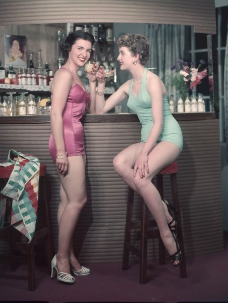 Two smiling, leggy young models enjoy a drink together at a cocktail bar. A towels is slunged nonchalantly over a bar stool. I hope they don't intend to drink & swim!