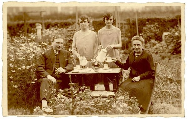 A French family poses for a photograph whilst enjoying coffee in their garden