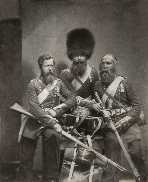 Three Coldstream Guards posing in uniform, with their weapons, in a photograph entitled Crimean Braves. The men are Joseph Numa, John Potter and James Deal. This is one of a series of photographs of soldiers taken for Queen Victoria in the summer of 1856