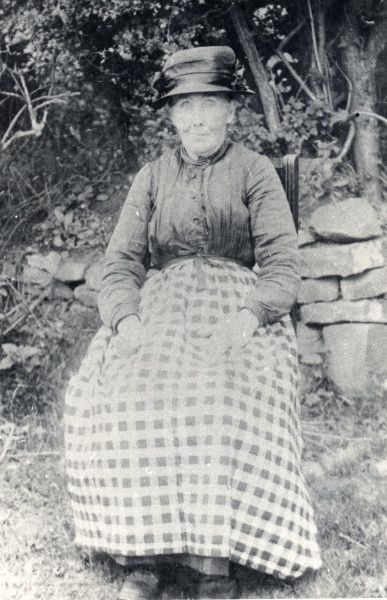 The elderly wife of a miner from Hook Colliery, near Haverfordwest, Pembrokeshire, South Wales. She is sitting on a chair in a garden, and appears surprised to be having her photograph taken