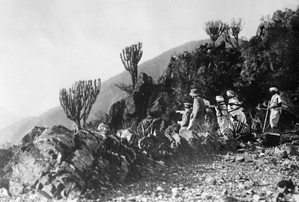 Native Libyan troops in Tripoli, North Africa, receiving directions in the mountains from European, probably Italian, officers. Date: 1930s