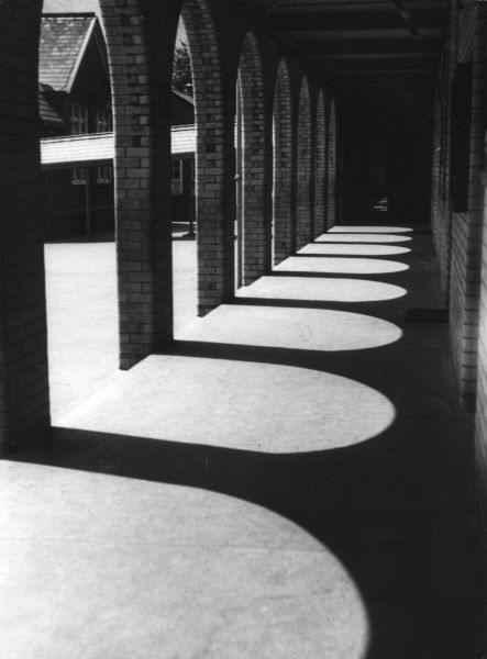A pattern of sun and shadow along a colonnade. Date: 1930s