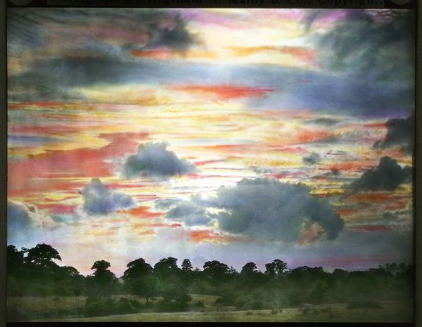 A colourful scene of a sky with clouds, above a country landscape