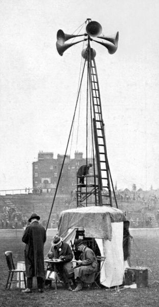 Photograph of a loud speaker being used at Stamford Bridge football stadium. The man seated at the table spoke into the telephone receiver and his voice was broadcast through the six speakers to the spectators
