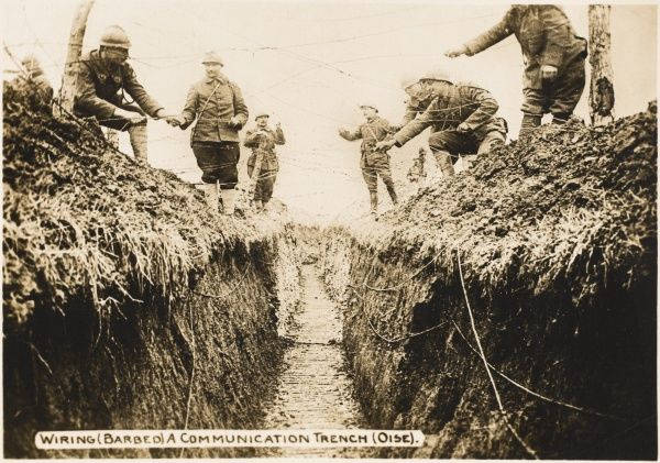 Placing barbed wire over a communications trench on the Oise during World War I