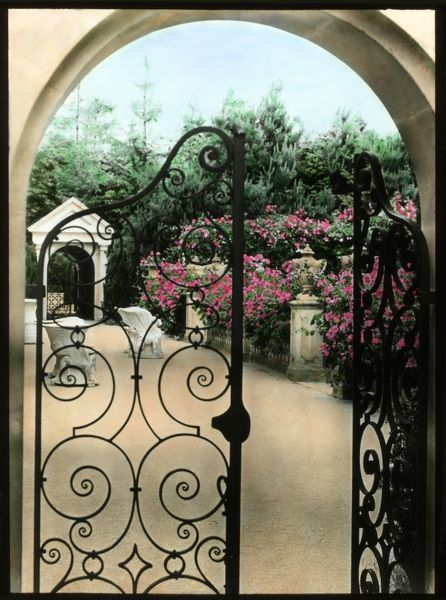 View of Compton Acres Gardens in the village of Canford Cliffs, near Poole, Dorset. Bright pink flowers can be seen through an archway with a wrought iron gate