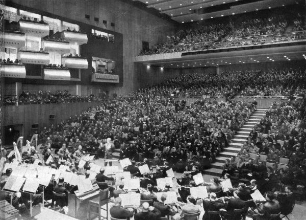 Scene inside the new Royal Festival Hall, on the South Bank, London, with one of the first concerts taking place. The auditorium, balcony and boxes are almost full, and an orchestra is in place on the platform. Photograph taken from the choir seats