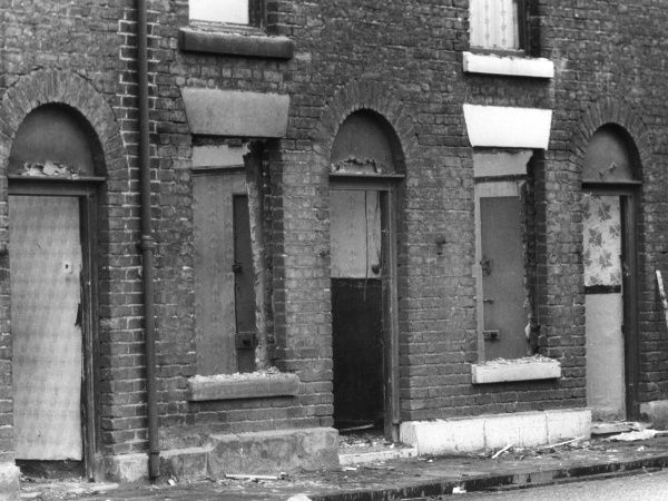 Condemned slum terraced houses in the North of England, abandoned and boarded up, ready for demolition. Date: 1960s