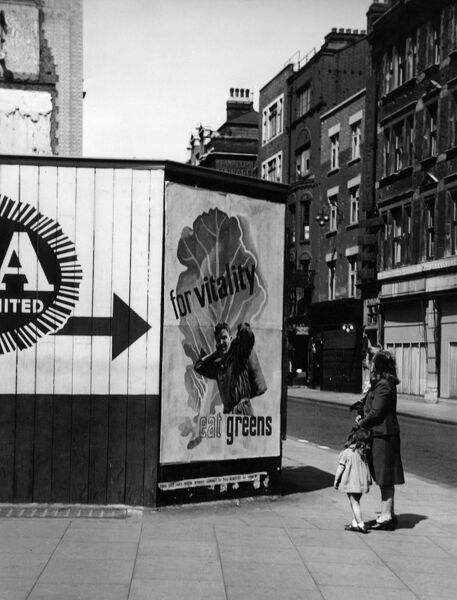 A woman and her little girl contemplate a large poster advising the British population to eat greens 'for vitality' in an unidentified London street c. 1945. c.1945